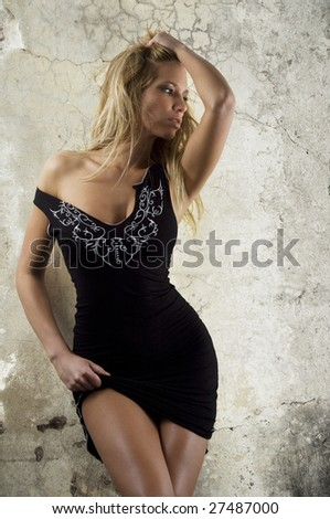 beautiful woman in black dress in front of wall - stock photo