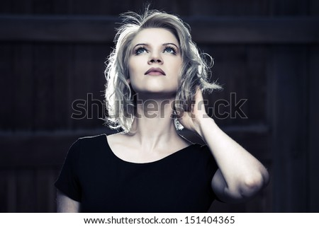 Beautiful woman in black dress looking up - stock photo