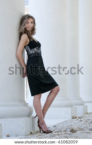 Beautiful woman in black dress near column