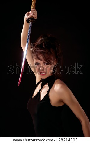 Beautiful woman in black dress with katana sword - stock photo