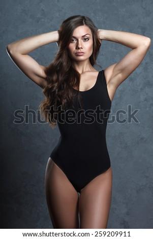beautiful woman in black leotard posing on grey background - stock photo