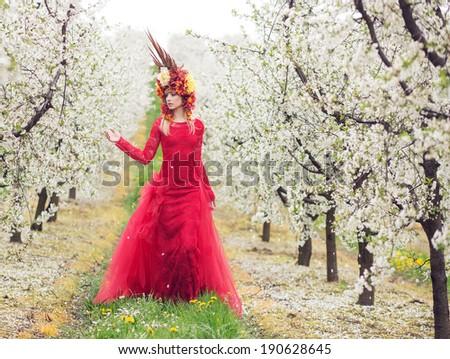 Beautiful woman in blooming orchard - stock photo