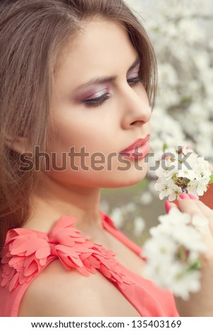 Beautiful woman in blooming spring garden