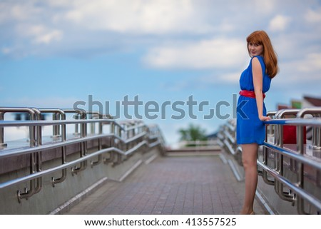 Beautiful woman in blue dress and red belt standing on the bridge