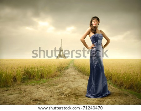 Beautiful woman in blue dress with Eiffel Tower on the background - stock photo