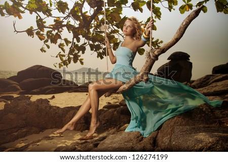 Beautiful Woman In Blue Fluttering Dress Swinging On A Beach Swing - stock photo
