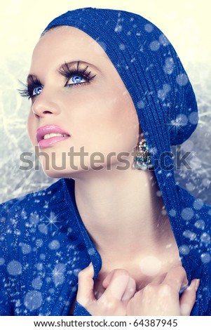 beautiful woman in blue jacket and snow falling around her - stock photo