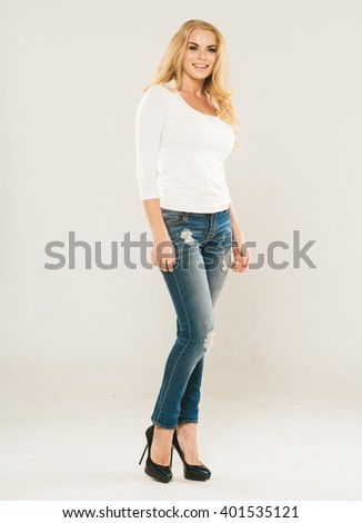 Beautiful woman in blue jeans with curly blonde hair portrait studio on white