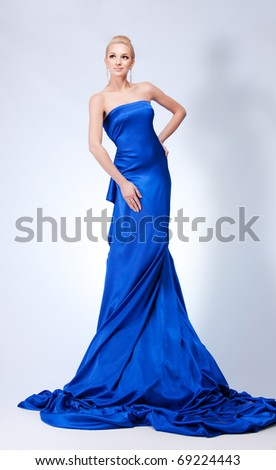 Beautiful woman in blue on gray background - stock photo
