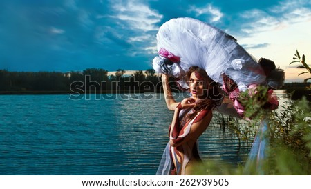 Beautiful woman in bodyart on the river sunset  background - stock photo