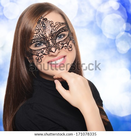Beautiful woman in carnival mask over blue background - stock photo