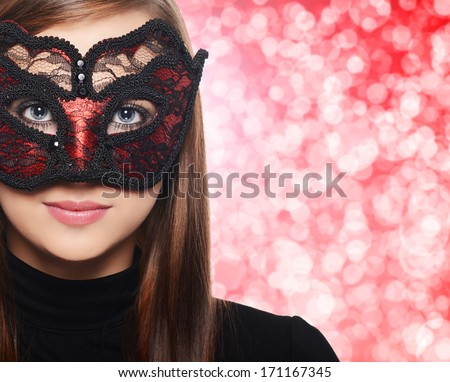 Beautiful woman in carnival mask over red bokeh background - stock photo