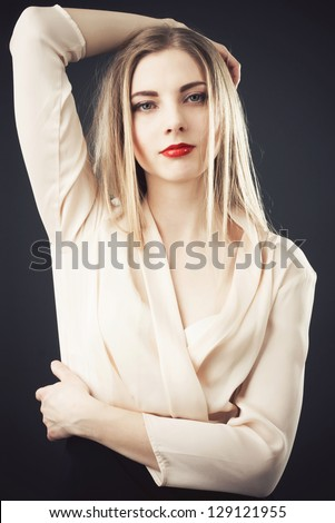Beautiful woman in chiffon beige blouse against black background - stock photo