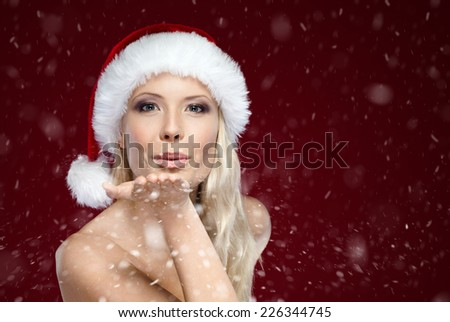 Beautiful woman in Christmas cap blows kiss, isolated on purple - stock photo