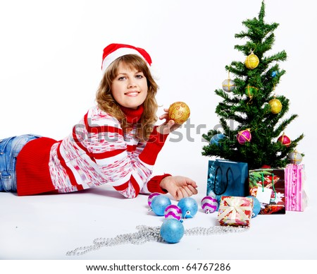 beautiful woman in christmas hat decorates a christmas tree