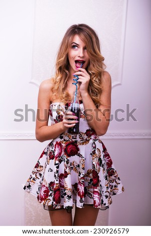 Beautiful woman in colour dreass posing with drink in studio  on white wall background - stock photo