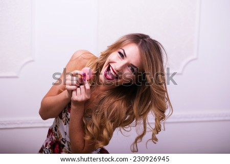 Beautiful woman in colour dress eating macaroons in studio - stock photo