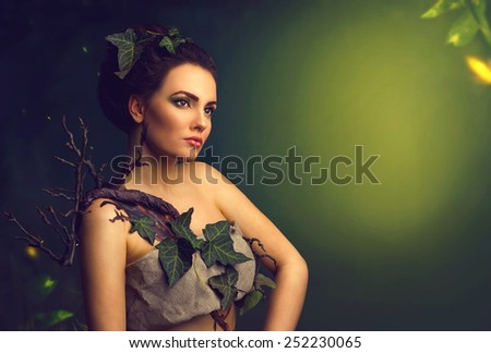 Beautiful woman in concept costume nature forest tree elf on green background with copyspace  - stock photo