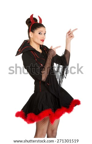 Beautiful woman in devil carnival costume pointing aside. - stock photo