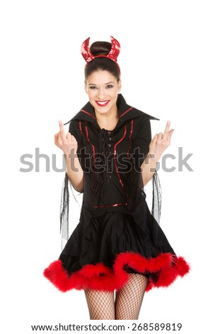 Beautiful woman in devil carnival costume with thumbs up. - stock photo