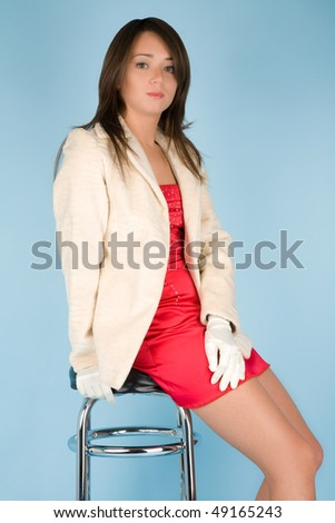 Beautiful woman in dress and fur sitting on the barchair - stock photo