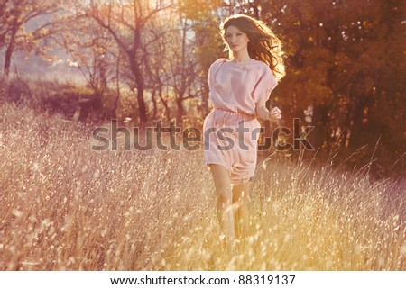 Beautiful woman in dress runing in the autumn forest - stock photo