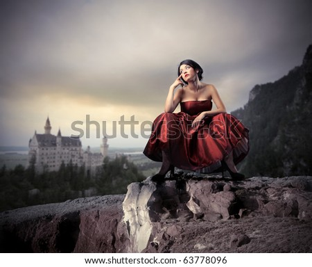 Beautiful woman in elegant dress with fabulous castle on the background - stock photo