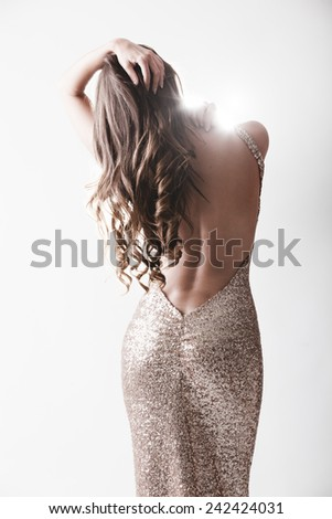 Beautiful woman in elegant expensive evening shiny dress with naked rear - stock photo