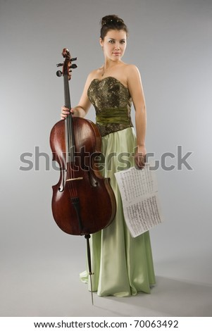 Beautiful woman in evening dress with cello and score - stock photo