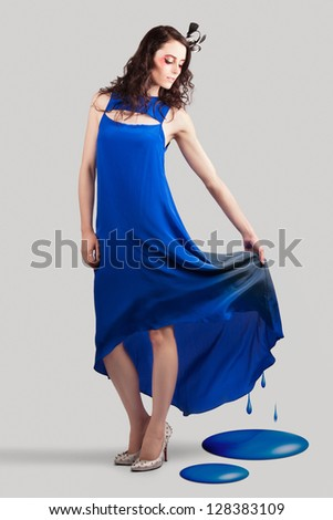 Beautiful Woman In Fashion Studio With Dress Melting To Blue Paint In A Depiction Of Fashion Colour Trends - stock photo