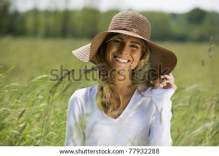 Beautiful woman in field with straw hat - stock photo