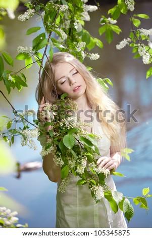 Beautiful woman in flower garden - stock photo
