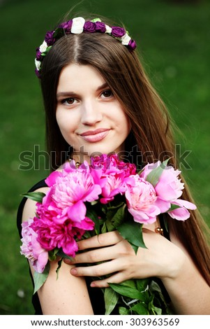 Beautiful woman in flower headband outside. Young fashionable hippie girl outdoor. Enjoy nature. Laughing and happy. - stock photo