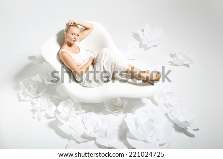 Beautiful woman in flowers .Beautiful young woman sitting on a white chair surrounded by stylish white flowers  - stock photo
