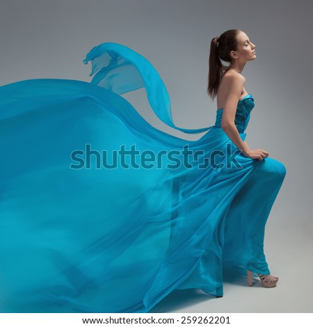 Beautiful woman in fluttering airy blue dress. Gray background. - stock photo