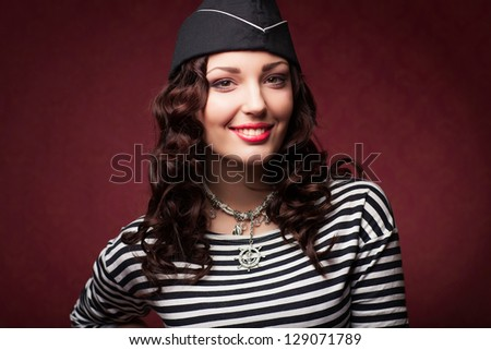 beautiful woman in forage-cap and frock smiling, studio shot - stock photo