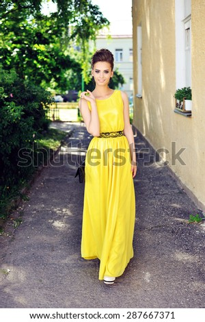Beautiful woman in full length posing in long yellow party dress - stock photo
