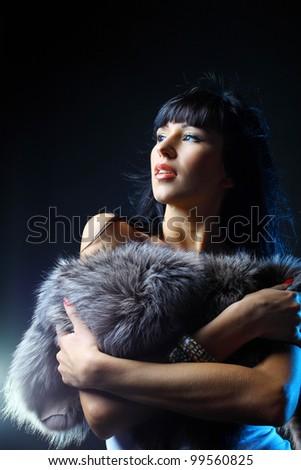 Beautiful woman in fur dress against dark background - stock photo