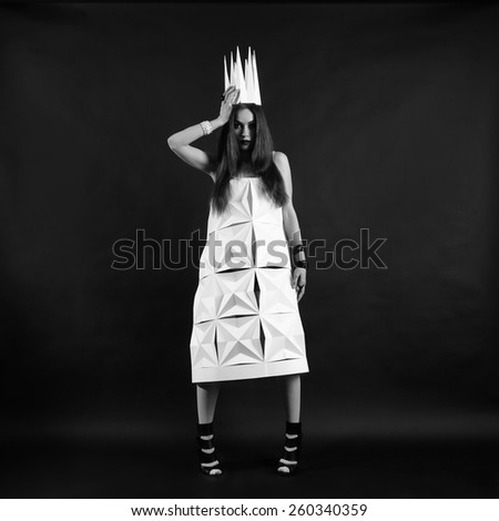 Beautiful woman in geometrical dress in crown. Fashion black and white portrait of queen.
