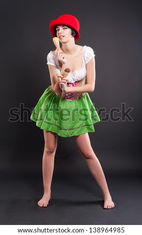 Beautiful woman in german beer girl costume with ice cream at black background - stock photo