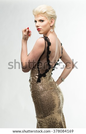 Beautiful woman in gold gown on white backdrop