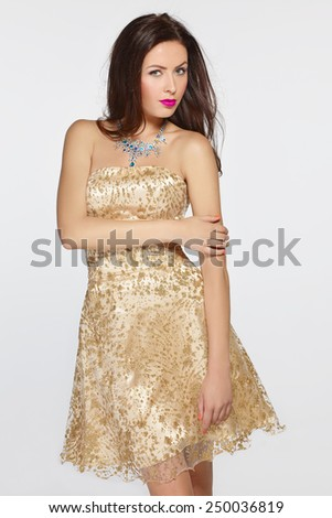 Beautiful woman in golden evening dress - stock photo