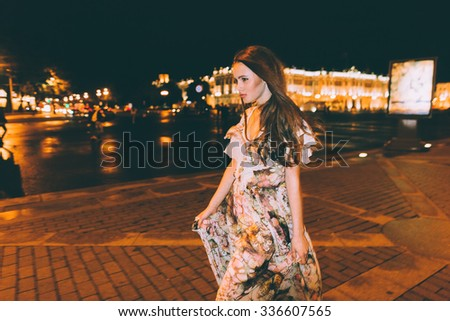 Beautiful woman in gorgeous dress against the backdrop of the city at night. Motion effect. - stock photo