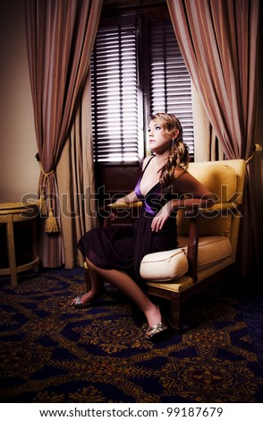 Beautiful Woman In Gorgeous Fashion Watching Movie In A Stylish Hotel Room With Discomfort, Anxiety And  Fascination In A Edge Of Your Seat Entertainment Concept - stock photo