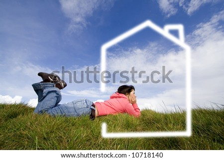 beautiful woman in grass dreaming with new house - stock photo