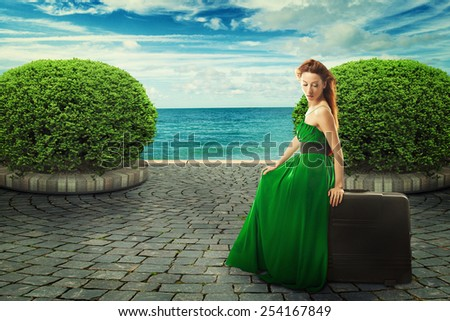 Beautiful woman in green dress sitting on a suitcase  - stock photo