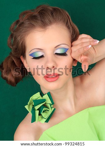 Beautiful woman in green. ?losed eyes - stock photo