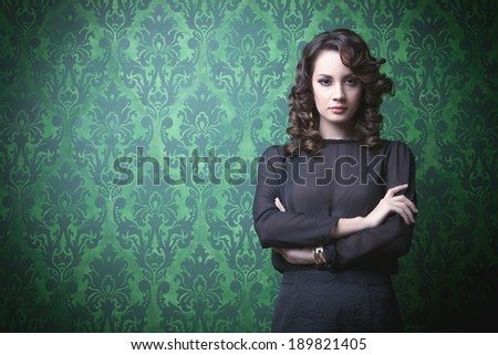 Beautiful woman in green vintage room. Professional make up and hairstyle. Retro rich interior. Toned image - stock photo