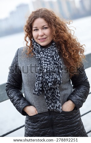 Beautiful woman in grey coat portrait, long curly hair, hands in pockets - stock photo