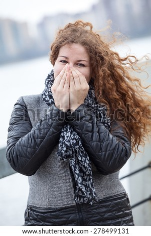 Beautiful woman in grey coat warming her hands while standing on cold wind - stock photo
